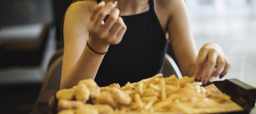 Close up of teenage girl eating french fries